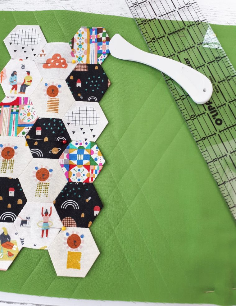 Use a quilting ruler and hera marker to mark the stitch lines for quilting.