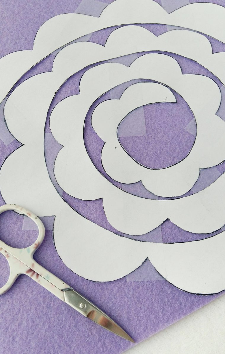 How to tape a paper pattern on felt to cut out a DIY rolled felt flower
